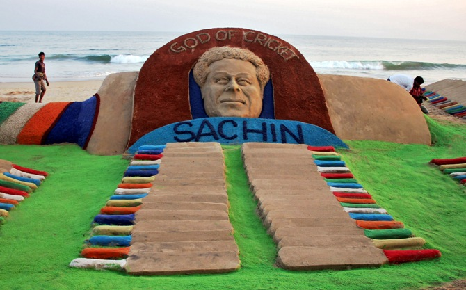 People walk past a sand sculpture of cricketer Sachin Tendulkar created by Indian sand artist Sudarshan Patnaik on a beach in Puri.