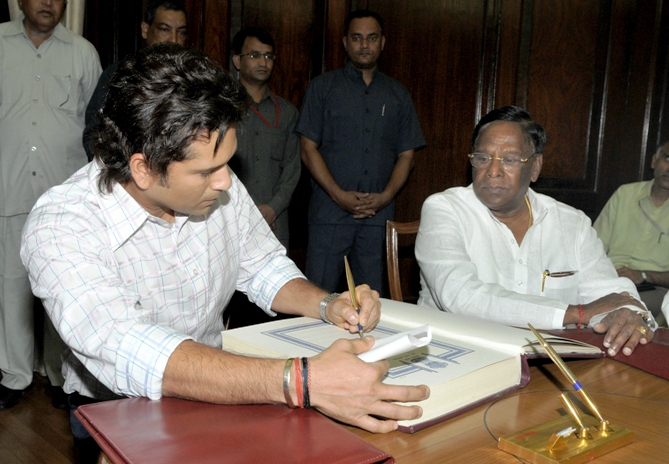 Sachin Tendulkar (L) signs the oath book as India's Minister of State for Parliamentary Affairs V Narayanasamy watches during the swearing-in ceremony at the Indian parliament in New Delhi June 4, 2012.