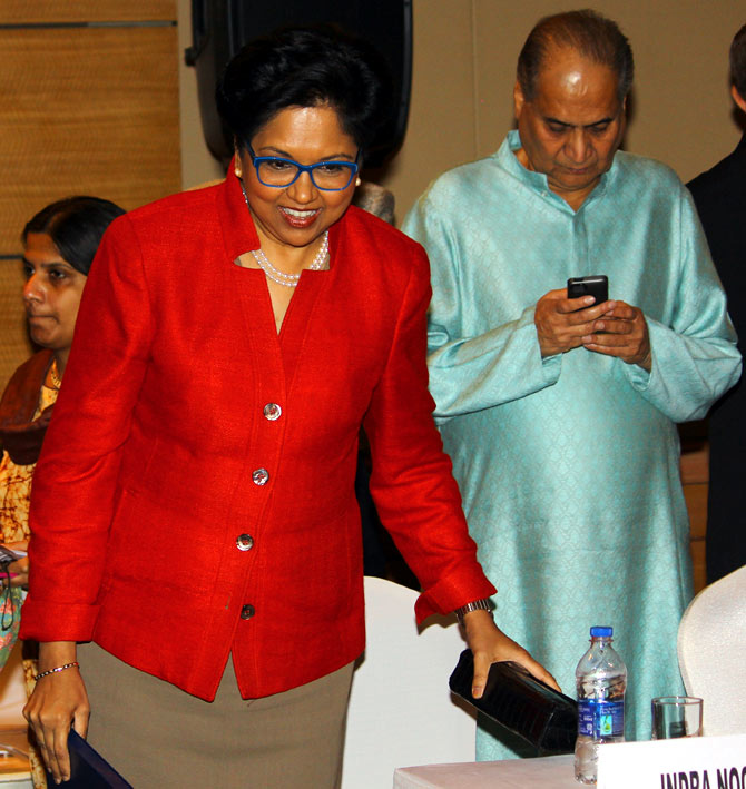 As Rahul Bajaj checks messages on his mobile phone, Nooyi prepares to take her seat.
