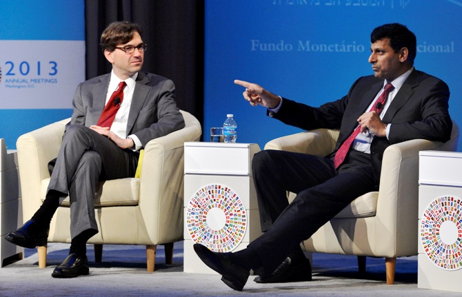 Reserve Bank of India Governor Raghuram Rajan (R) gestures as he responds to a question as Chairman of the Council Economic Advisers Jason Furman listens during a CNN Debate on the Global Economy, as part of the IMF and World Bank's 2013 Annual Fall Meetings, in Washington October 10, 2013.