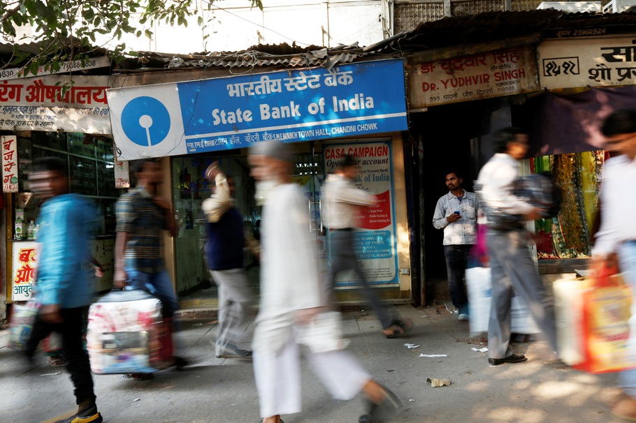 Commuters walk past a State Bank of India branch in the old quarters of Delhi November 13, 2013.