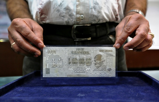 A jeweller poses with a silver plate in the form of an Indian rupee note inside a showroom in New Delhi.