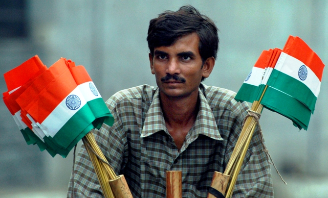 A hawker sells national flags on the eve of Independence Day in New Delhi.