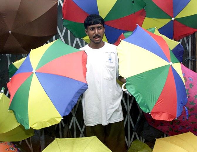 Sanjoy Panja, a street hawker, sells umbrellas in Kolkata.