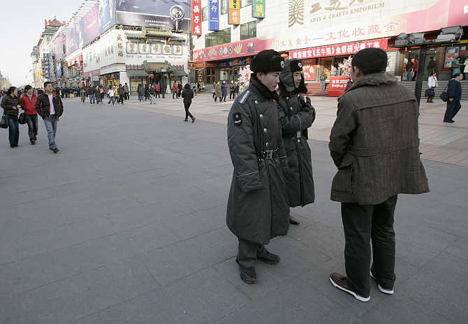 Security guards talk with a passer-by on Wangfujing street in Beijing, China.