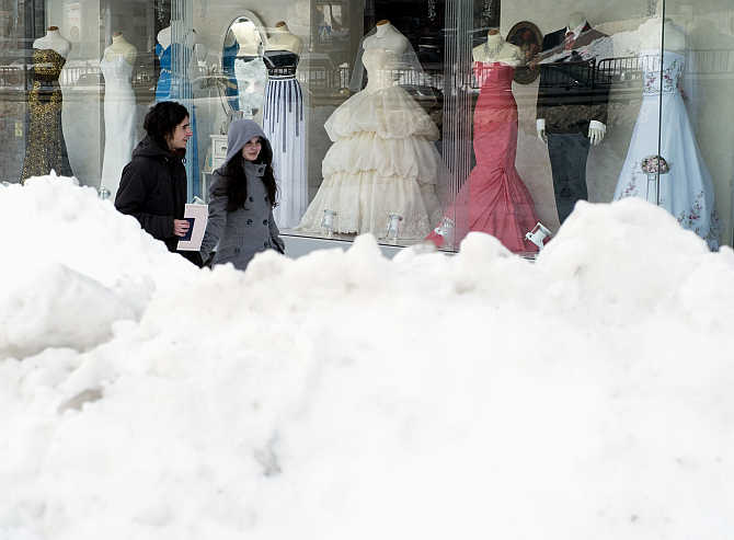 People walk past a shop window displaying wedding dresses after an unusually heavy snowstorm in Kiev, Ukraine.