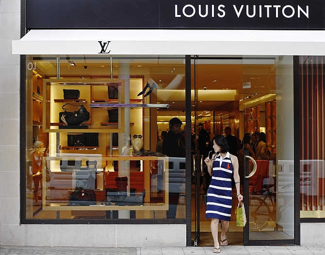 A woman exits the Louis Vuitton shop on New Bond Street in London, United Kingdom.