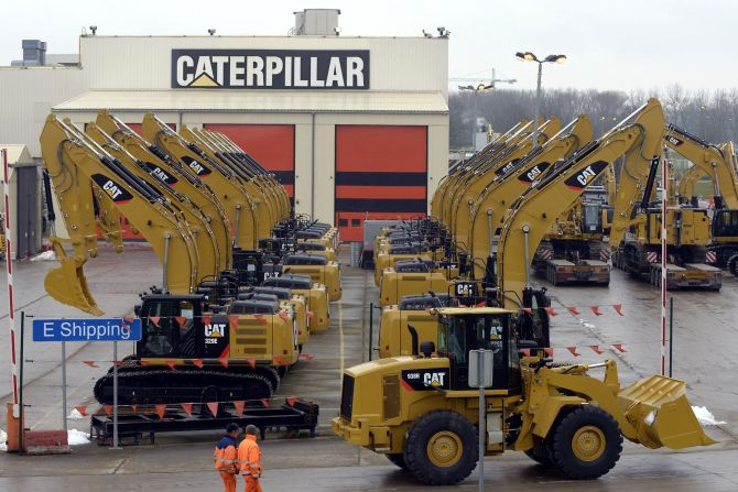 Workers walk past Caterpillar excavator machines at a factory.