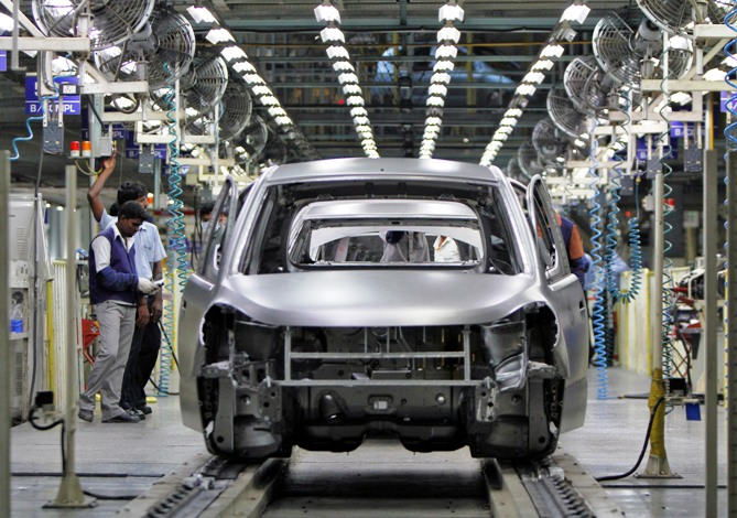 Workers stand next to the assembly line of the Hyundai Motor India Ltd plant at Kancheepuram district in Tamil Nadu.