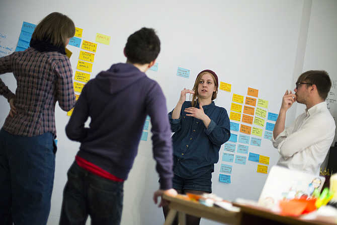 Employees of HowDo, a start-up, attend a production meeting in Berlin, Germany.