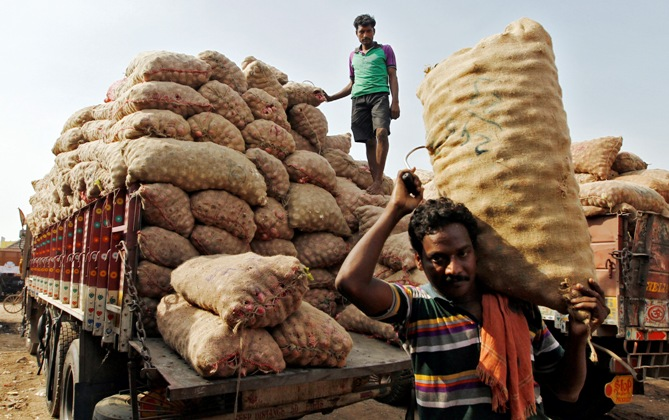 Labourers unload sacks filled with onions at a wholesale vegetable market in Chennai.