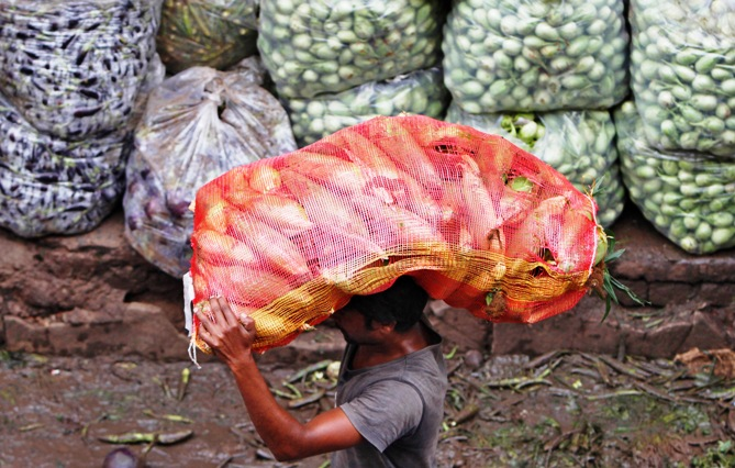 A man carries a sack filled with maize at a wholesale vegetable market in Ahmedabad.