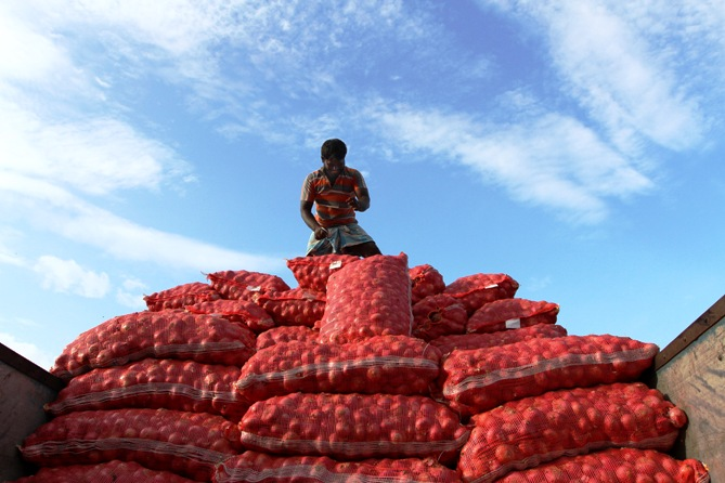 A labourer unloads sacks of onions from a supply truck at a vegetable wholesale market in Chennai.