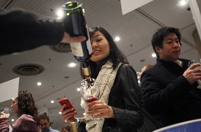 A woman gets a sample of red wine from Spain at the New York Wine Expo.