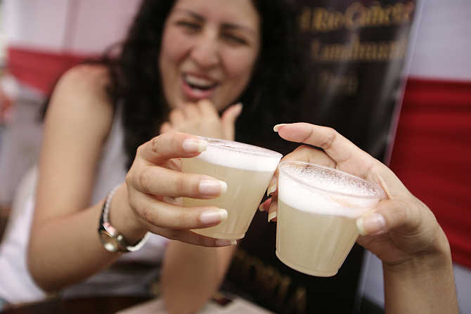 Women toast with traditional Peruvian drink Pisco Sour at Pisco Sour festival in Lima, Peru.
