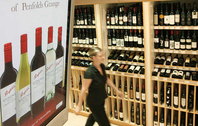 A woman walks into a wine store past an advertisement for Penfolds Grange wines in central Sydney, Australia.