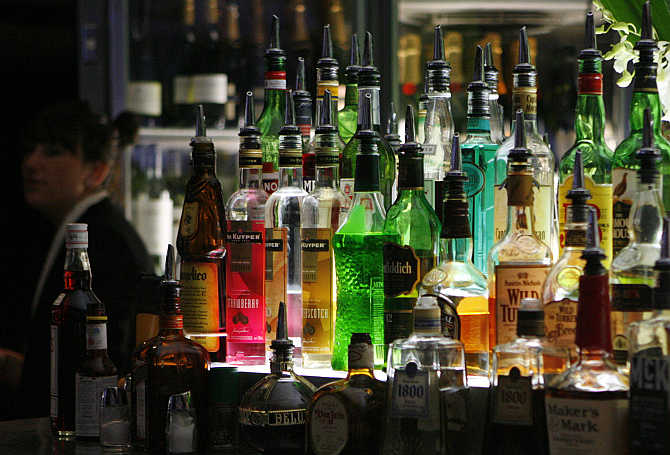 Bartender walks next to liquor bottles in a bar in central sydney