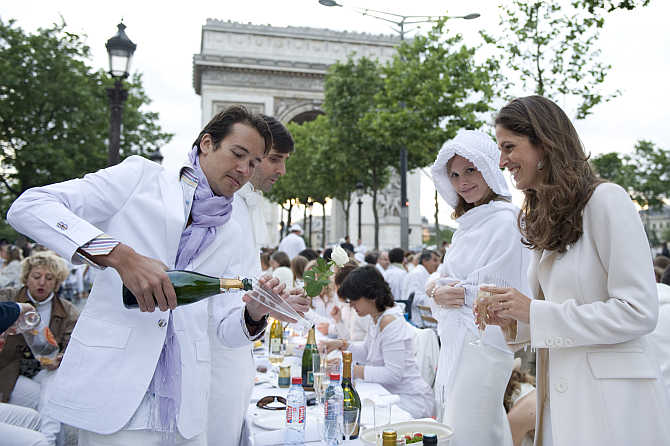 People attend the White Dinner event at the Champs Elysee near the Arc de Triomphe in Paris, France.