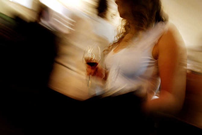 A woman holds a glass of red wine during a wine testing event in Santiago, Chile.