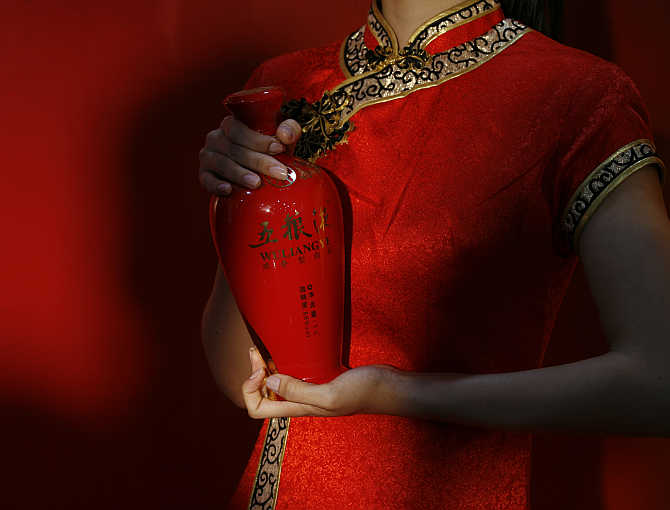 An attendant holds a bottle of Wuliangye during the opening of its flagship store in Hong Kong.