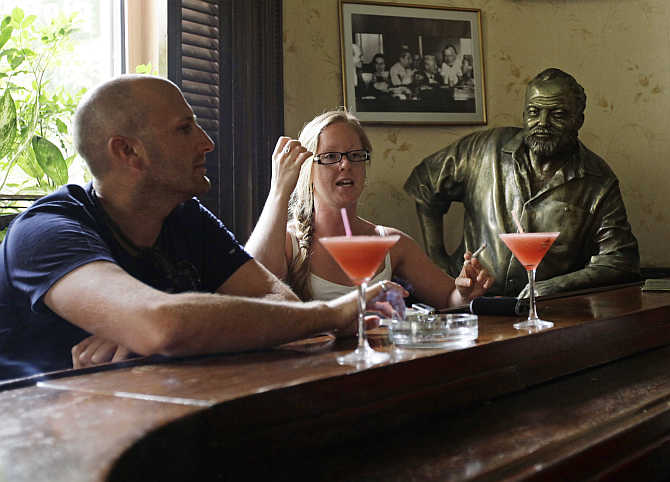 Tourists sit in front of their Daiquiris beside a life-size bronze statue of US writer Ernest Hemingway at his regular spot in The Floridita bar in Havana, Cuba.