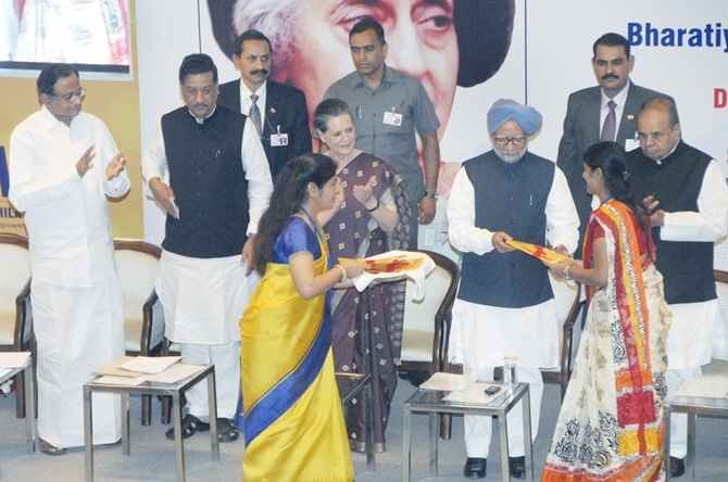 Prime Minister Manmohan Singh presents the new account kit to the first account holder, at the inauguration of the first branch of Bharatiya Mahila Bank.