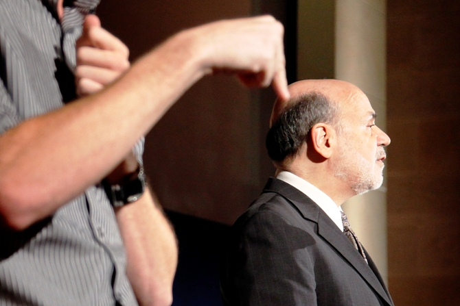 A sign language interpreter translates remarks by US Federal Reserve Chairman Ben Bernanke (R) at the National Economists Club annual dinner at the US Chamber of Commerce in Washington, November 19, 2013.