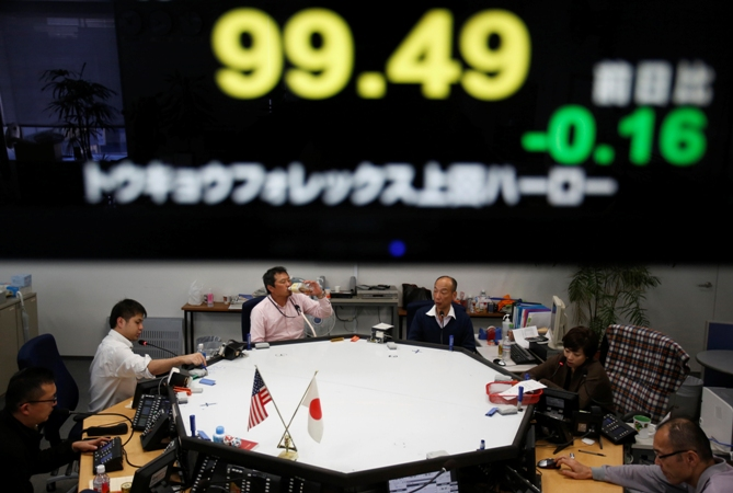 Employees of a foreign currency company work under a screen displaying the Japanese yen's exchange rate against the US dollar, at a dealing room in Tokyo November 13, 2013.