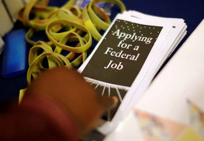 A man picks up a leaflet at a job fair in Los Angeles, California, November 18, 2013.