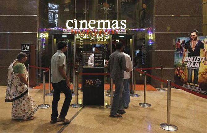 Cinema-goers queue for a security check at a PVR Multiplex in Mumbai.