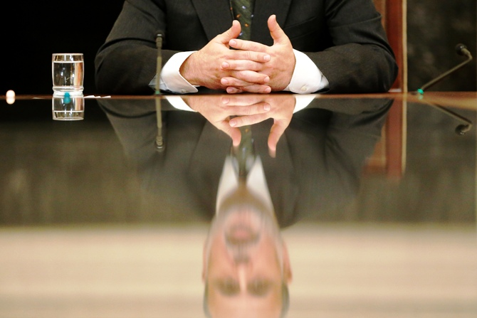 US Federal Reserve Chairman Ben Bernanke is reflected in a glass table top as he holds town hall event for teachers at the Federal Reserve Board's building in Washington November 13, 2013.