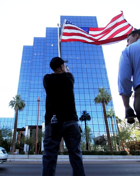 A man waves the U.S. flag as others gather during a protest against Senate Bill 1070 (SB-1070), in front of the Immigration and Customs Enforcement offices in Phoenix, Arizona.