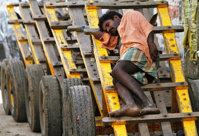 A labourer takes a nap on a wooden cart at a wholesale vegetable market in Chennai.
