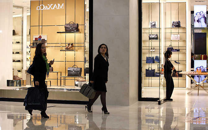 Women walk past a shop selling luxury shoes and bags at a mall in Jakarta, Indonesia.