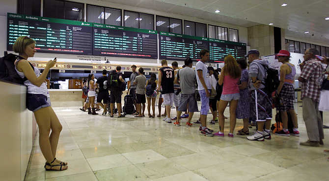A passenger uses her mobile phone as others queue in front of an information counter at a railway station in Barcelona, Spain.