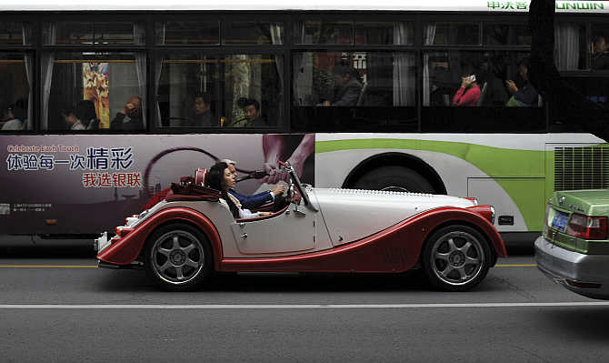 Charles Morgan and his wife Kiera Morgan drive a Morgan sport car during the opening of China's first Morgan sport cars showroom in Shanghai.