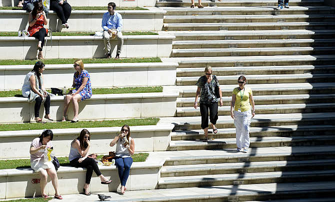 People sit in the sun in Sheldon Square in west London, United Kingdom.