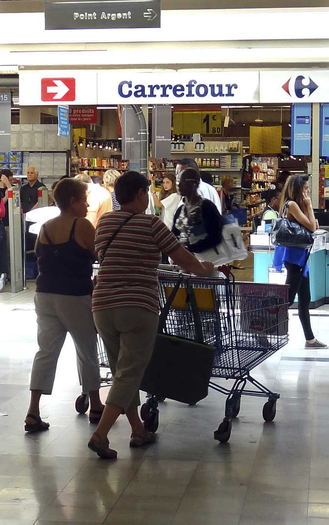 Customers push shopping trolley as they enter a Carrefour supermarket in Montreuil near Paris, France.