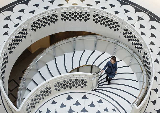 A gallery assistant poses for photographs on the spiral staircase at Tate Britain in central London, United Kingdom.