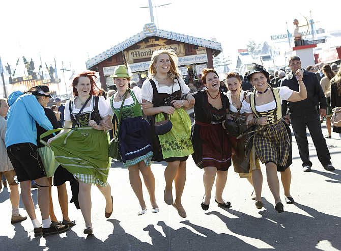 Young women pose while wearing traditional Bavarian dirndls at Munich's beer festival, Germany.