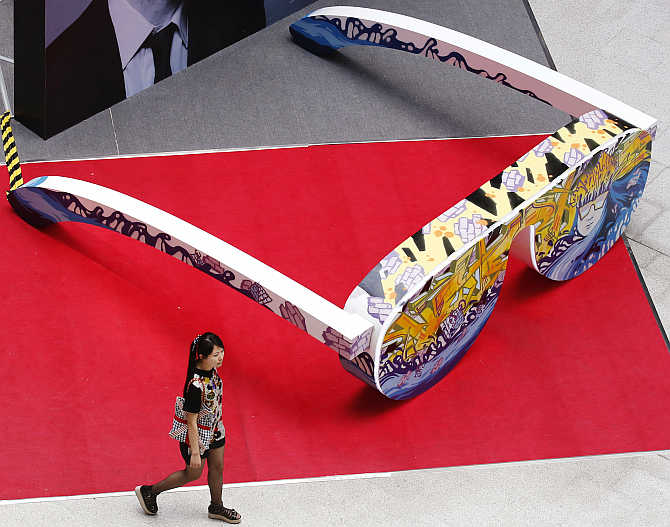A woman walks past an installation shaped like a pair of sunglasses at a shopping mall in Beijing, China.