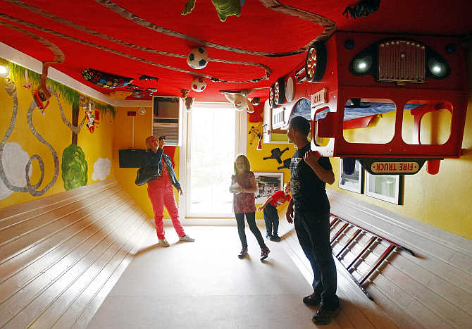 People stand inside a room of a house, which was built upside down by Polish architects Irek Glowacki and Marek Rozhanski, in the western Austrian village of Terfens.
