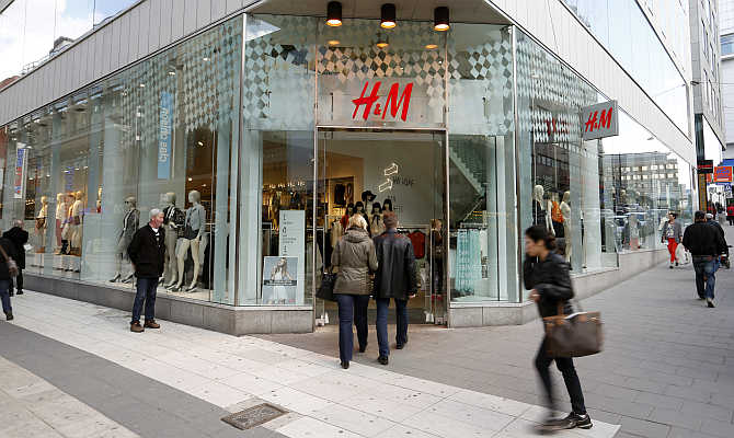 People walk past a branch store of H&M in Stockholm, Sweden.