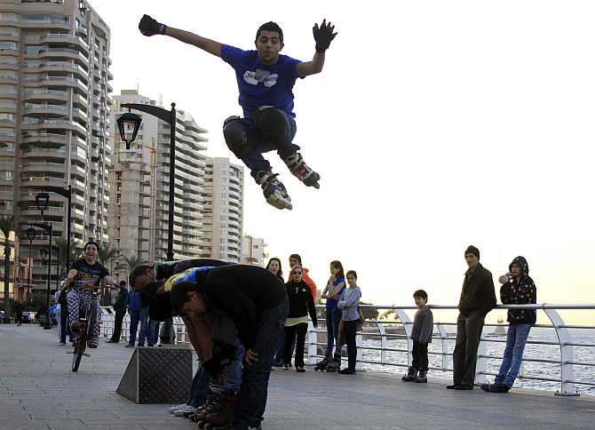 A boy jumps over his friends as he skates on roller blades in Corniche Al Manara on the Beirut Riviera, Lebanon.