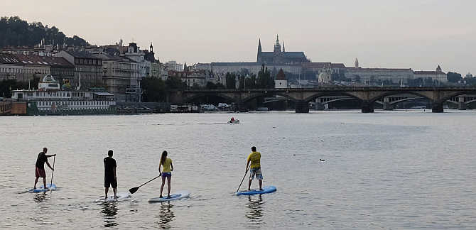 People paddle on their boards on the Vltava river in central Prague, Czech Republic.