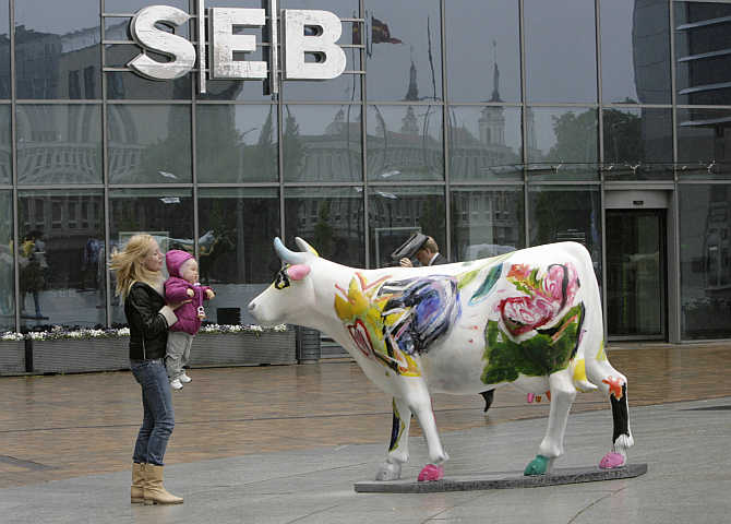A woman lifts a child to look at a painted model of a cow in front of SEB bank branch in Europa business centre in Vilnius, Lithuania.
