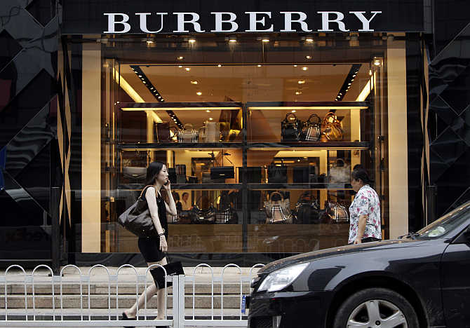 Women walk past a Burberry shop in Beijing, China.