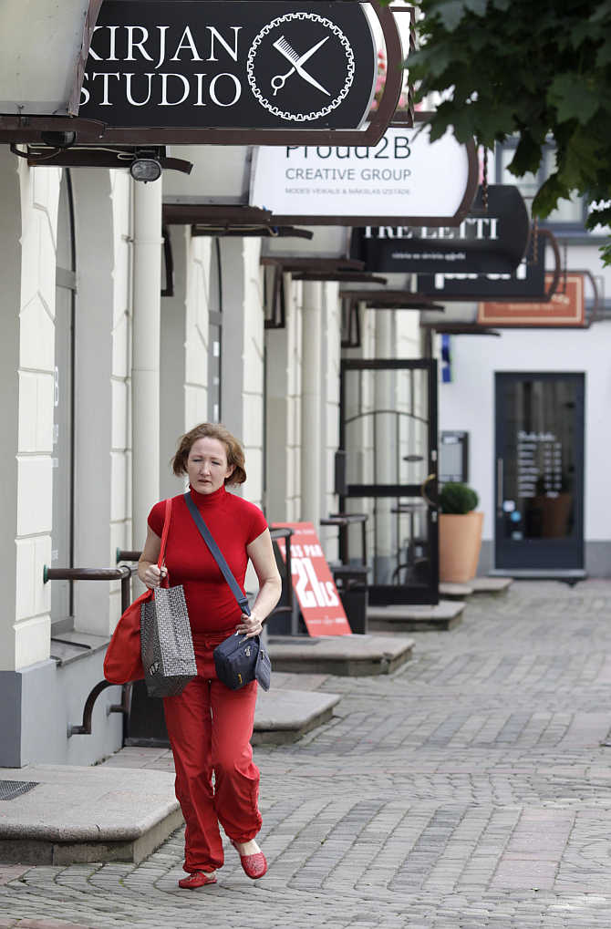 A woman holds a shopping bag as she walks past shops in Riga, Latvia.