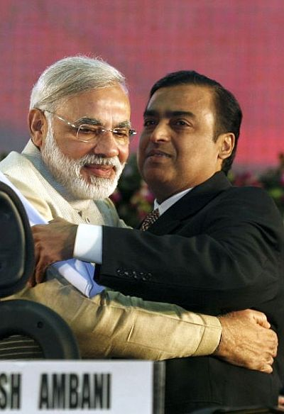 Gujarat's chief minister Narendra Modi (L) embraces Mukesh Ambani, chairman of Indian energy company Reliance Industries, during the Vibrant Gujarat Global Investors' Summit.
