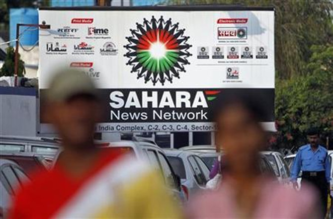 Commuters walk past a billboard advertising the Sahara News Network, along a road in Noida on the outskirts of New Delhi.